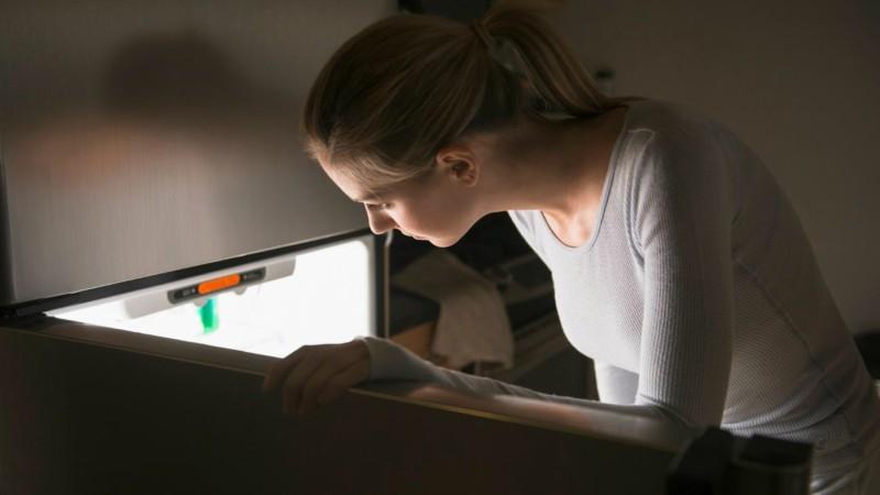 mulher abrindo geladeira defrost