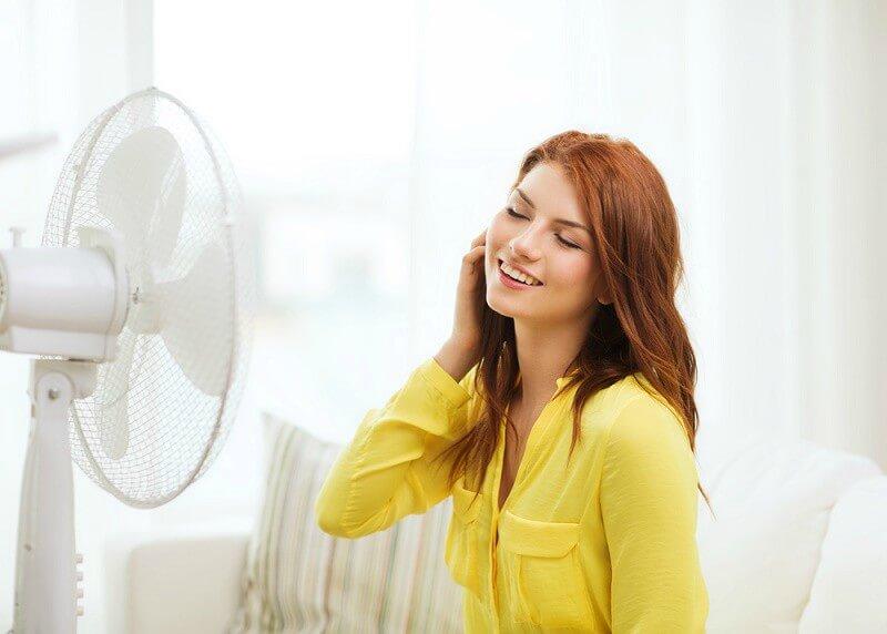 Moça se refrescando com um ventilador