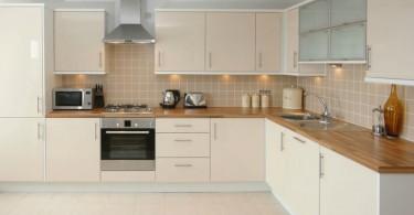 Cozinha mobilhada com móveis e paredes em tons claros