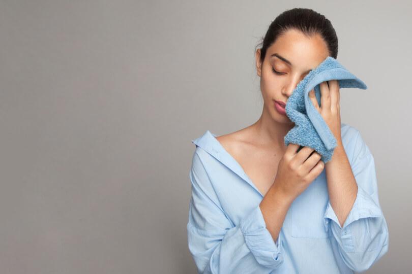 Mulher secando o rosto após limpeza de pele