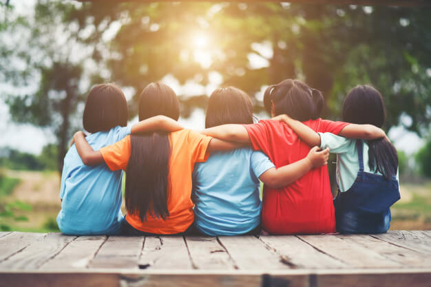 crianças sentadas se abraçando