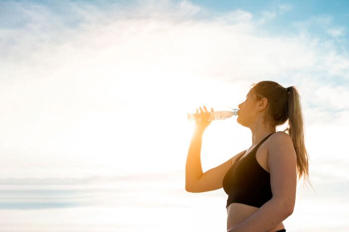 Mulher bebendo água na praia