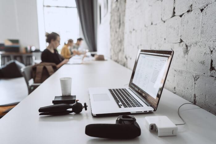 Notebook em escritório ao lado de carregador e outros aparelhos