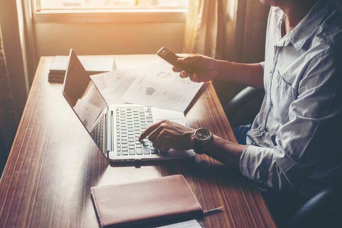 Profissional em escritório usando notebook e smartphone