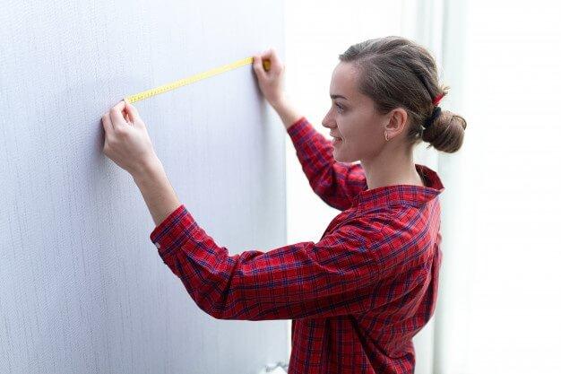 Mulher medindo parede para instalar ar-condicionado