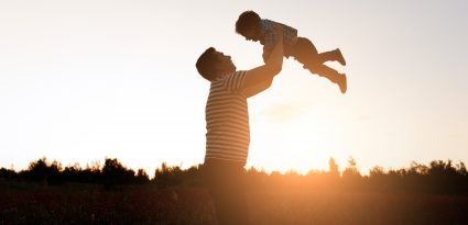 Pai e filho brincando no parque na hora por do sol